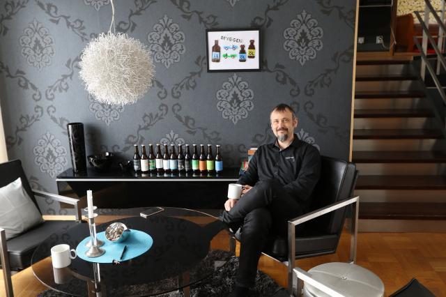 SIGNIFIKANT. Intill Andreas fikahörna finns hans ölsortiment presenterat. Möblerna har han givetvis gjort själv efter att noga ha hittat den rätta, sittriktiga, formen. – Pärltavlan på väggen är en julklapp från min systers barn med mina huvudintressen öl och Lotus Seven som motiv, säger Andreas Gustafsson.